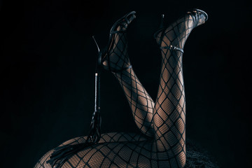Low key photo of sexy female nude legs in fetish nett tights and high heels shoes holding whip against dark background