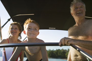 Young boy and his mature grandparents on a boat.