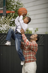 Father lifting his son up to a basketball hoop.