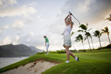Female golfer playing golf on a coastal golf course.