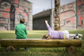 Two children sitting on a wooden bench.