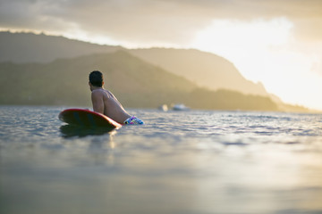 Male surfer balances on his surfboard in a calm sea with coastline in the background.