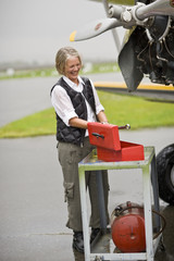 Mature woman fixing plane in the rain