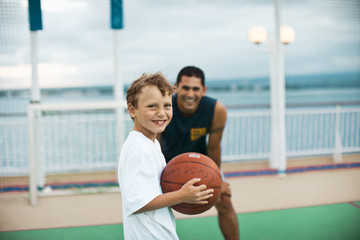 Boy holding a basketball and his basketball tutor smile as they pose for a portrait on a fenced seaside basketball court.