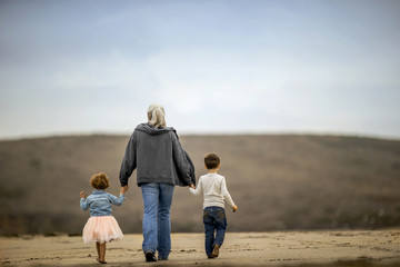 Mature woman walking on the beach with her grandchildren.