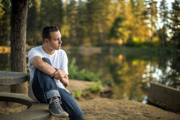 Young man sitting by lake.