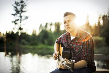 Young man playing guitar by lake.
