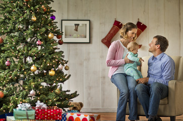 Couple and their baby sitting next to the Christmas tree.