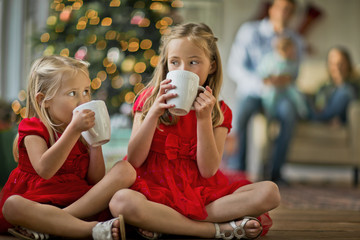 Two young girls drinking hot chocolates.