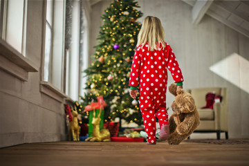 Young girl walking towards the Christmas tree with her teddy bear.