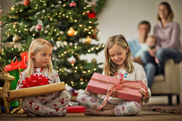 Two young girls with their Christmas presents.