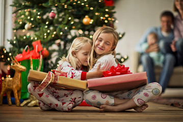 Two young girls hugging with their Christmas presents.