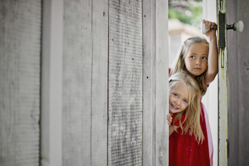 Two young girls peering around a doorframe.