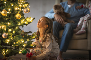 Young girl looking up at a decorated and illuminated Christmas tree.