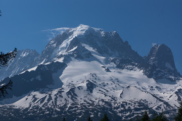 Mountain peaks with snow and light clouds. Summer in French Alps, MontBlanc