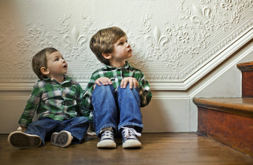 Two young boys looking up a staircase.