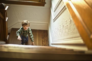 Young boy climbing up the staircase.