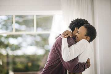 Happy young couple hugging in their new home.