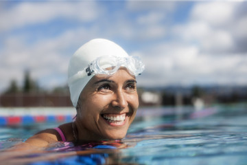 Happy mid adult woman smiling in a swimming pool.