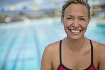 Portrait of a smiling middle aged woman by a the swimming pool.