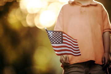 Young boy holding an American flag.