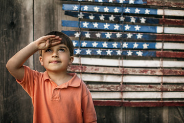 Proud young boy saluting in front of an American flag.
