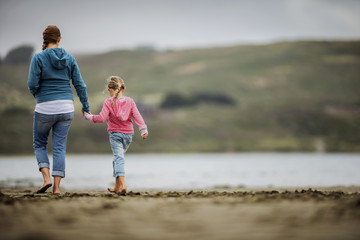 Young blond girl walks hand-in-hand with her mother along the beach.