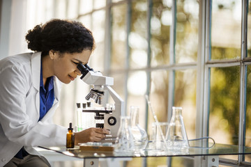 Scientist looking through a microscope at a sample.