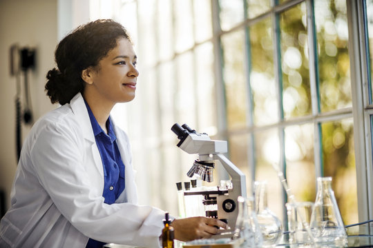 Scientist sitting in her laboratory with her microscope.