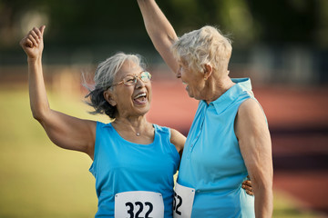 Two happy senior women laughing after competing in an athletic event.