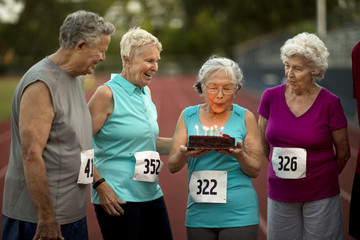 Happy senior friends celebrate a birthday before an athletics event.
