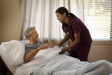 Smiling young nurse tucking in an elderly patient in a hospital bed.