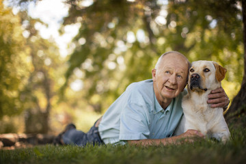 Happy elderly man lying down with his dog in a sunny garden.