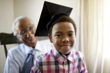 Young boy with graduation cap sitting with grandfather.