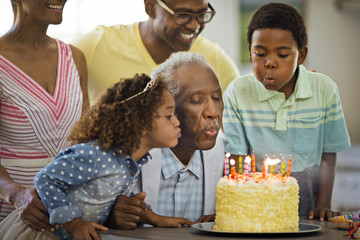 Senior man blowing out his birthday candles with his family.