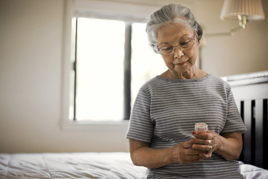 Senior woman sitting on her bed with a medicine bottle.