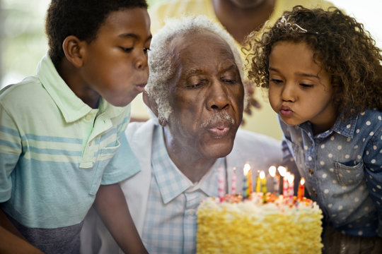 Senior man blowing out his birthday candles with his family