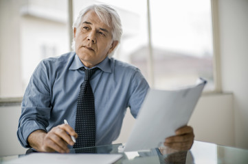 Focused businessman working in a corporate board room.