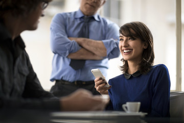 Smiling young businesswoman holds a cell phone while in a meeting with two colleagues.