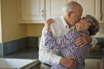 Elderly couple share a cheeky loving kiss in their kitchen.