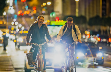 Middle-aged man and his pretty young girlfriend smiling as they cycle together along a busy city street at night.