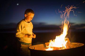 Boy looking at glowing campfire at the beach.