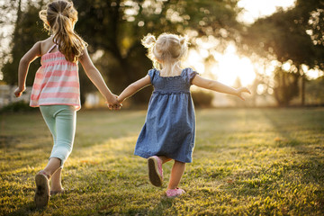 Siblings running hand in hand through a park.