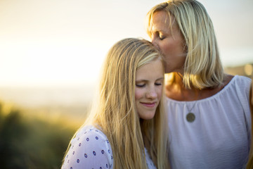 Middle aged woman kissing her teenage daughter on the forehead.