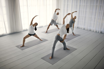 Small group of friends practicing yoga.