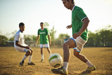 Group of young men playing soccer together on a dusty playing field in the sunshine.