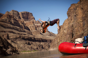 Young man back flipping off a raft into a river.