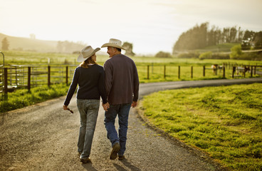 Happy mid adult couple smiling at one another while walking on a farm.