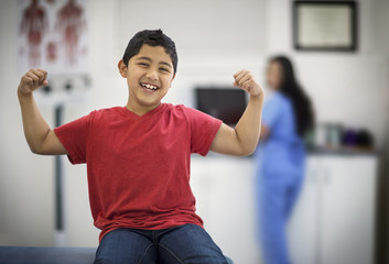 Portrait of a laughing young boy flexing his muscles while sitting inside a doctor's office.