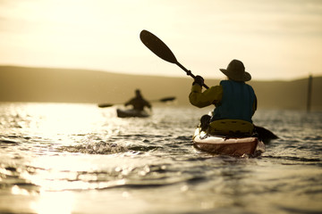 Happy senior couple kayaking together in the ocean at sunset.